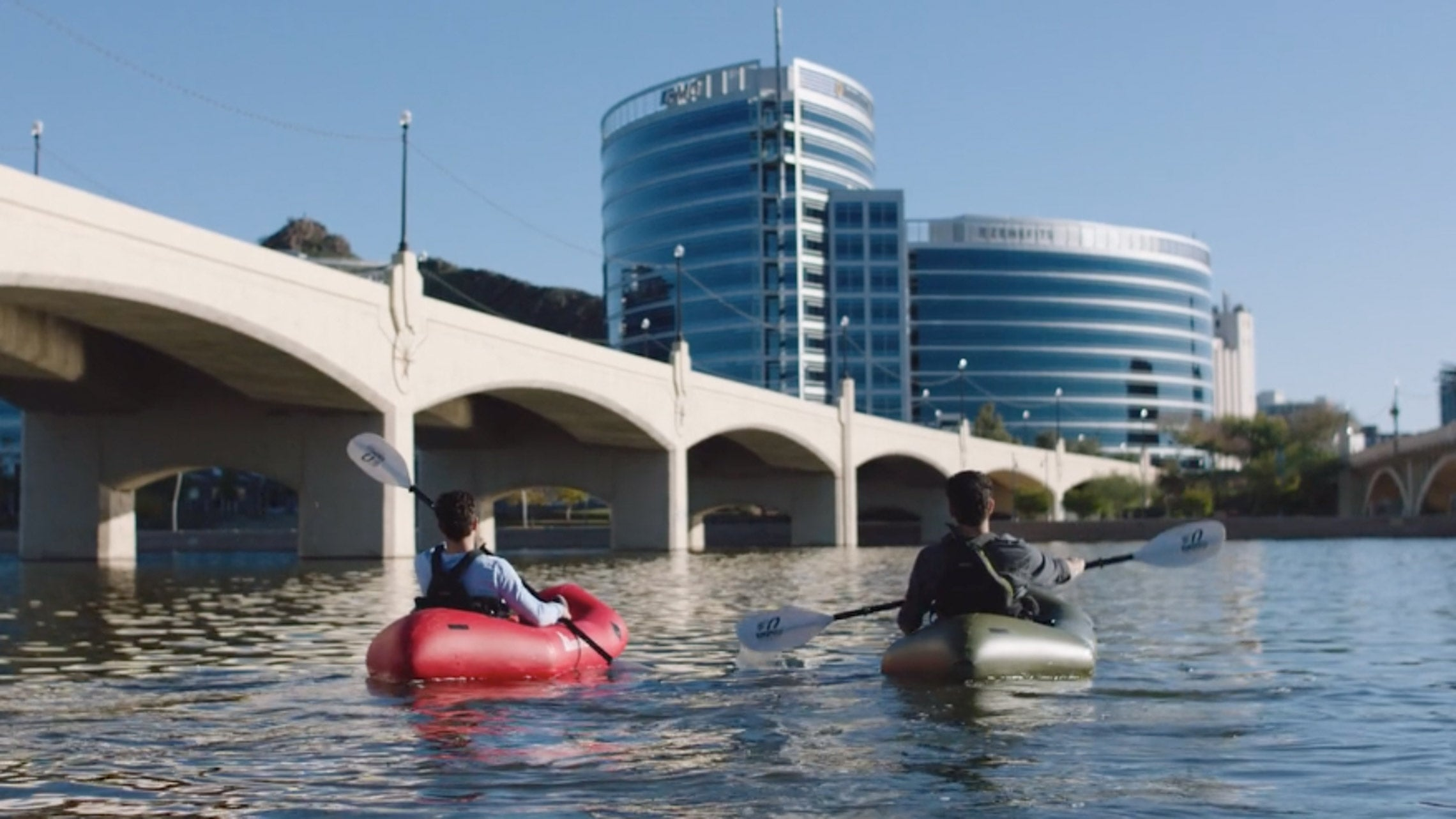 Friends packrafting in a city landscape. Kokopelli XPD Packrafting Adventures