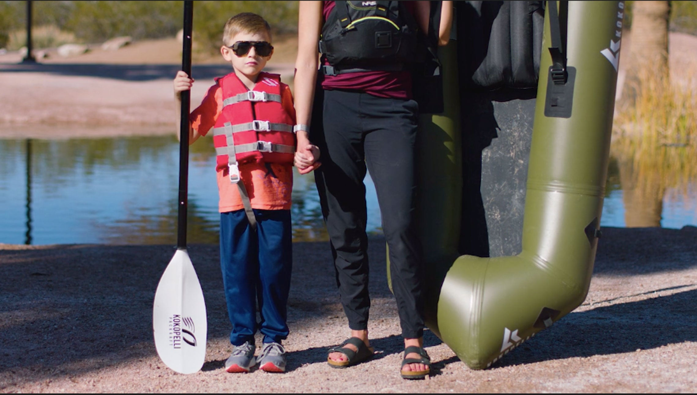 Little boy holding a paddle next to an adult holding the XPD Kokopelli Packraft