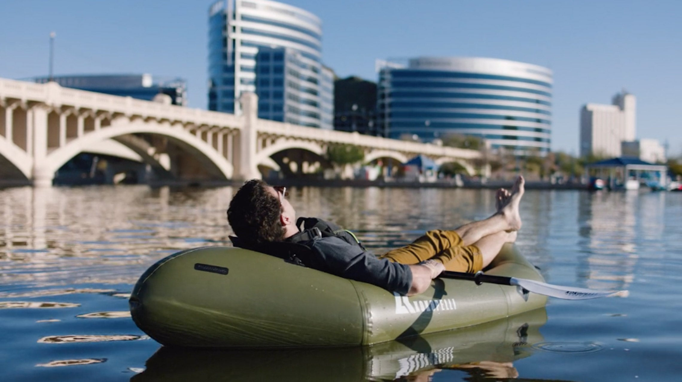 Man laying back in an XPD Kokopelli Packraft on water next to a city