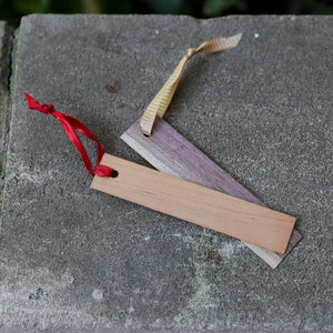 Two wood bookmarks with a ribbon tied on end on concrete