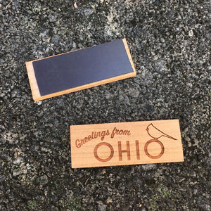 "Wood Magnet with ""Greetings from Ohio"" and a cardinal outline laser design on a concrete background"