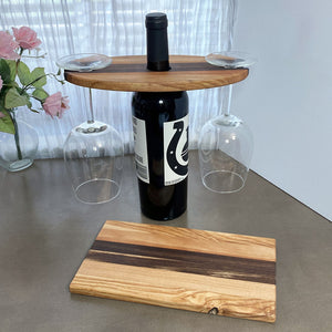 Wood Wine and Glass Display with a coordinating cheese board on a grey table and white window background
