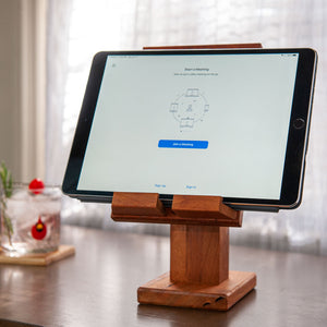 Adjustable Wood Tablet Stand one facing back on the left showing the wood hinge another next to it with a tablet on display sitting on concrete with a grass background