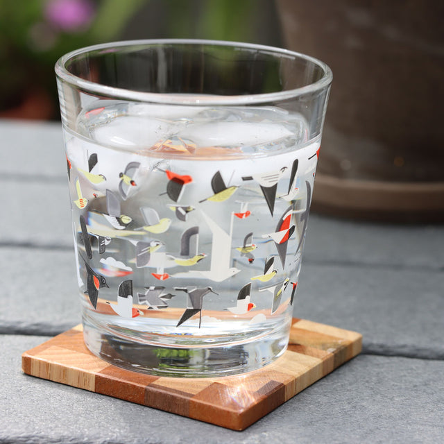 Wood coaster made from various woods a one of a kind on top rests a clear short glass with with Charlie Echo design