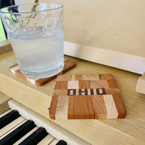 Wood Ohio coaster hand cut letters and pieces sitting on a piano