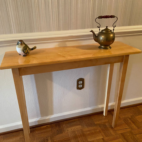 Maple console table with a bird figurine and teapot on display