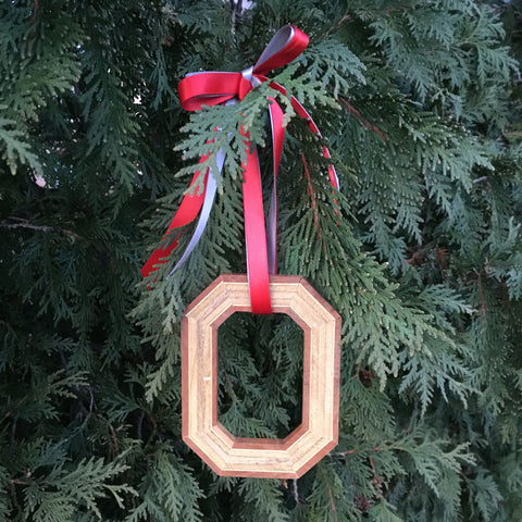 Block O wood ornament tied with scarlet and grey ribbons hanging on a pine tree.