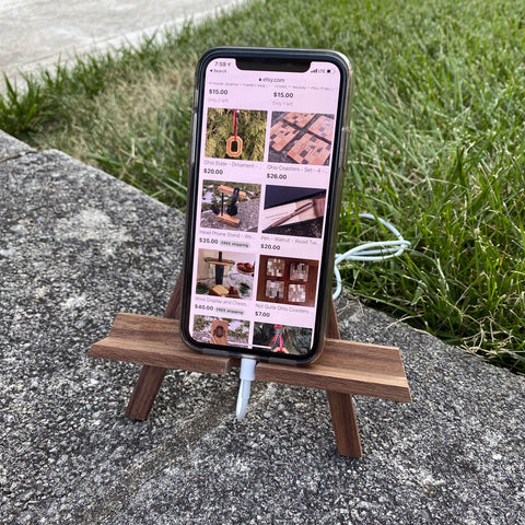 Walnut wood phone stand, easel. Displayed with a phone and charging access.