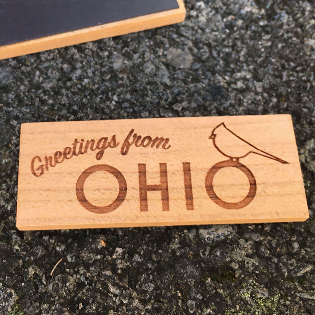 "Wood magnet with ""Greetings from Ohio"" engraved and a cardinal. One concrete background."
