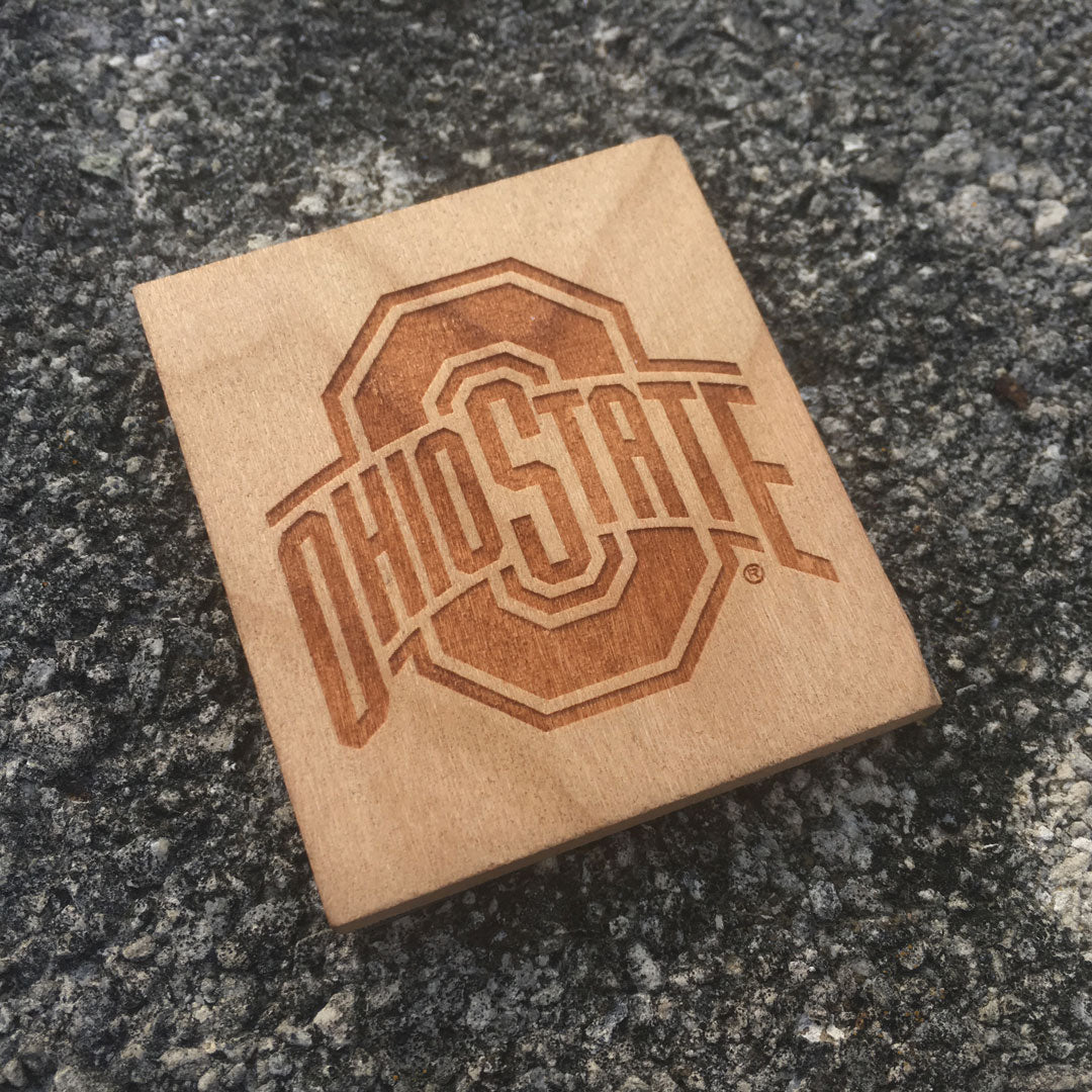 Ohio State sport logo wood magnet with a concrete background.