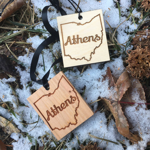 Wood ornament with laser engraved design, Athens text enclosed in the shape of Ohio. Snow and leaves in background.