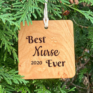 Best Nurse Ever Ornament on Pine Tree Background.