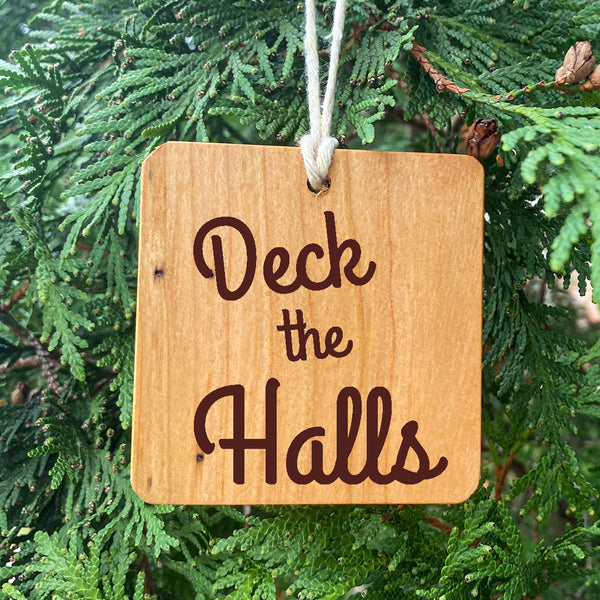 Deck the Halls Wood Ornament on pine tree background