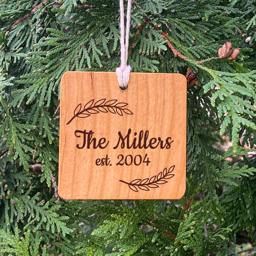 Wood Ornament laser engraved text The Millers est 2004 on pine tree background.