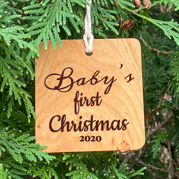 Baby's first Christmas wood ornament on pine tree background.