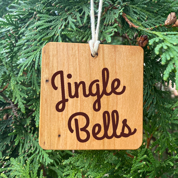 Jingle Bells text on a wood cut ornament on a pie tree.