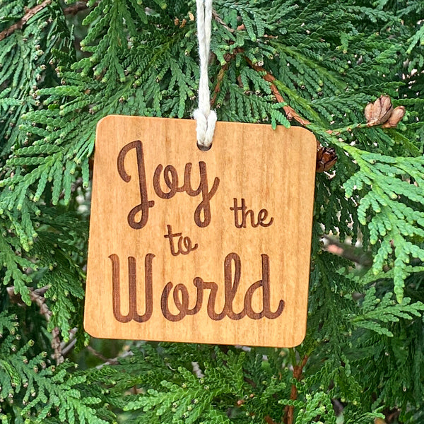 Hand cut wood ornament with Joy to the World laser engraved on a pine tree background.