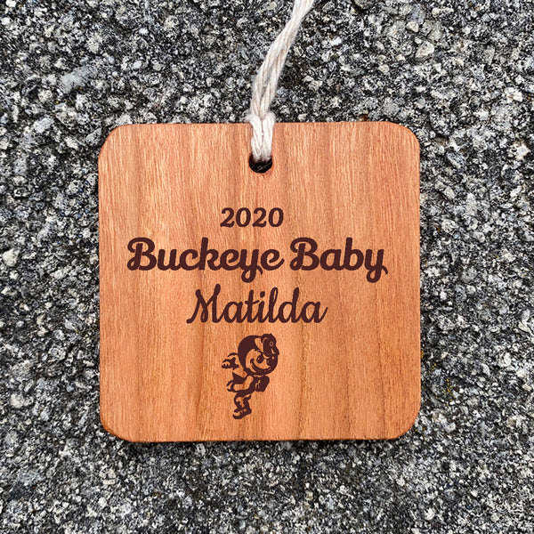 Wood Ornament with Buckeye Baby Matilda text engraved on concrete background.
