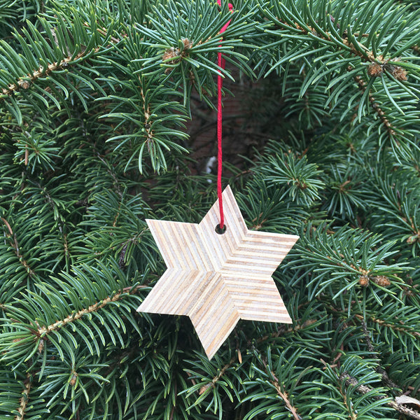 Small wood star Christmas ornament tied with a red string against a pine tree