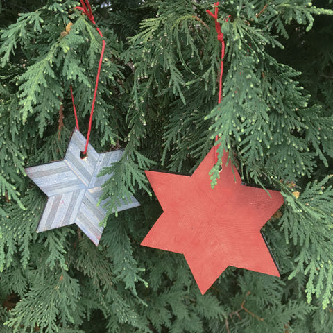 Two wood ornaments hanging from a pine tree. One gray and one scarlet.