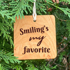 Smiling's my favorite ornament on pine tree background.