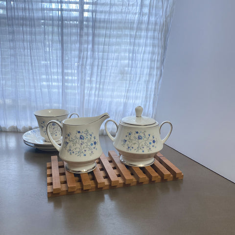 Wood trivet with creamer and sugar porcelain on top.