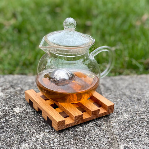 Small square wood trivet, a steaming teapot rests upon it.