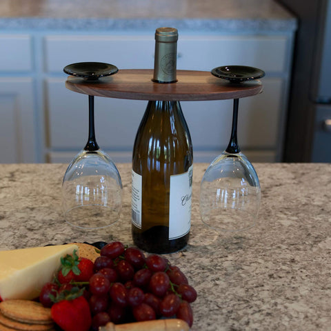 Walnut wood wine display with two wine glasses hanging and a wine bottle in the middle. Fruit and cheese plate in front.