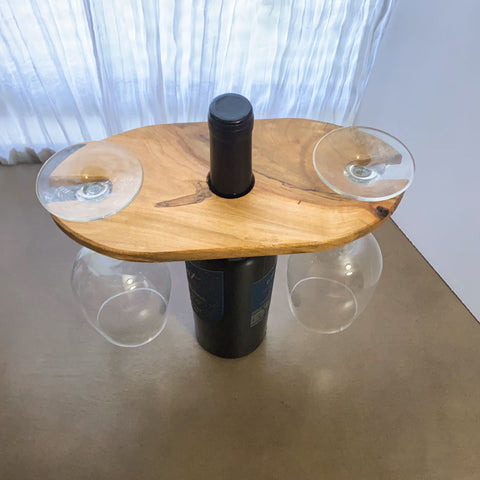 Wood wine and glass display, shown from an above angle with two glasses hanging from the display and a bottle in the center.