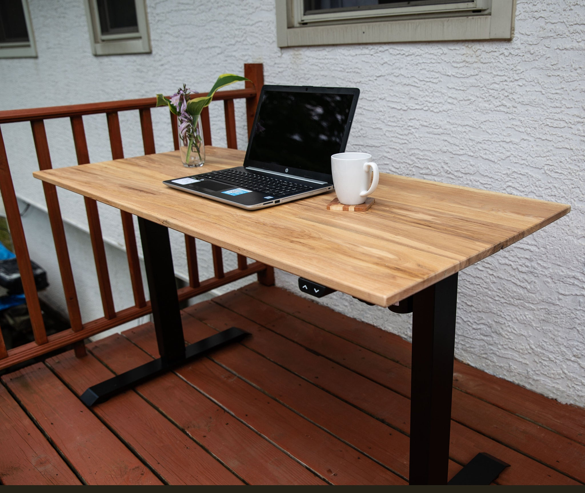 Electronic desk with ash wood top. Shown with a laptop, coaster and mug.