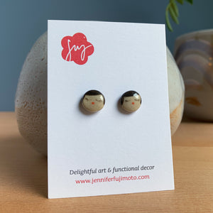 Ceramic earrings with cute peaceful expression on a backing card