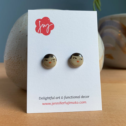 Ceramic earrings with cute side-eye expression on a backing card