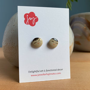 Ceramic earrings with cute faces on a backing card