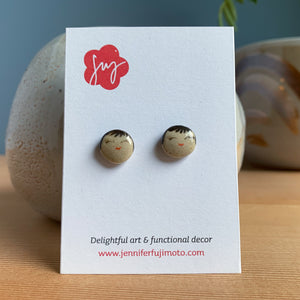 Ceramic earrings with cheerful expression on a backing card