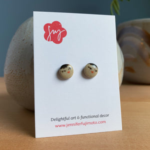 Ceramic earrings with cute coy expression on a backing card