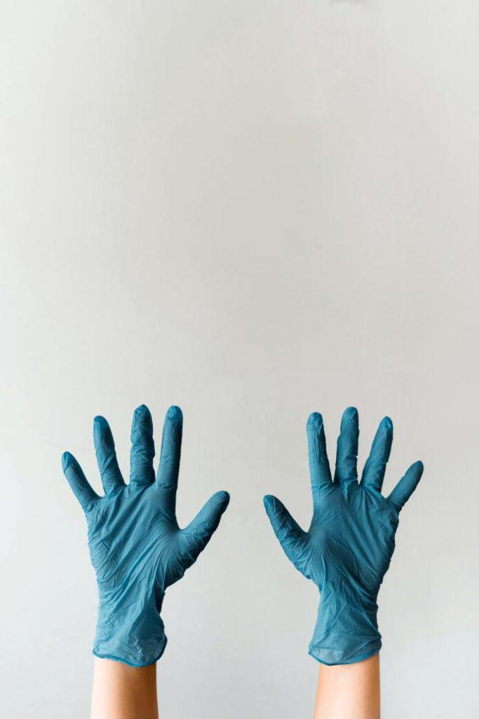 Pair of raised hands in blue surgical gloves