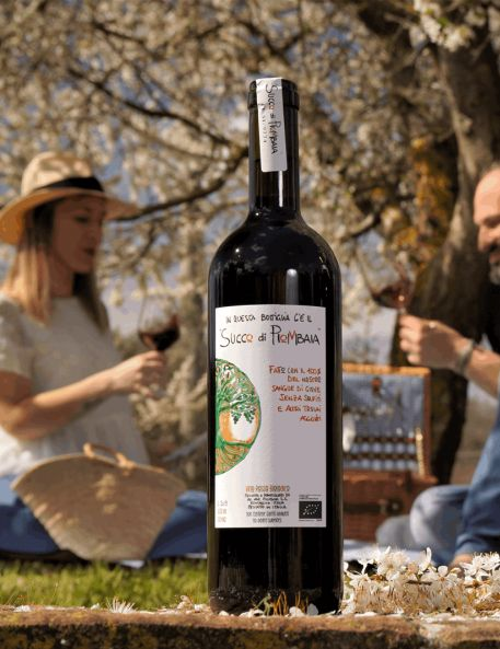 Bottle of wine in foreground with couple raising glasses under flowering trees.