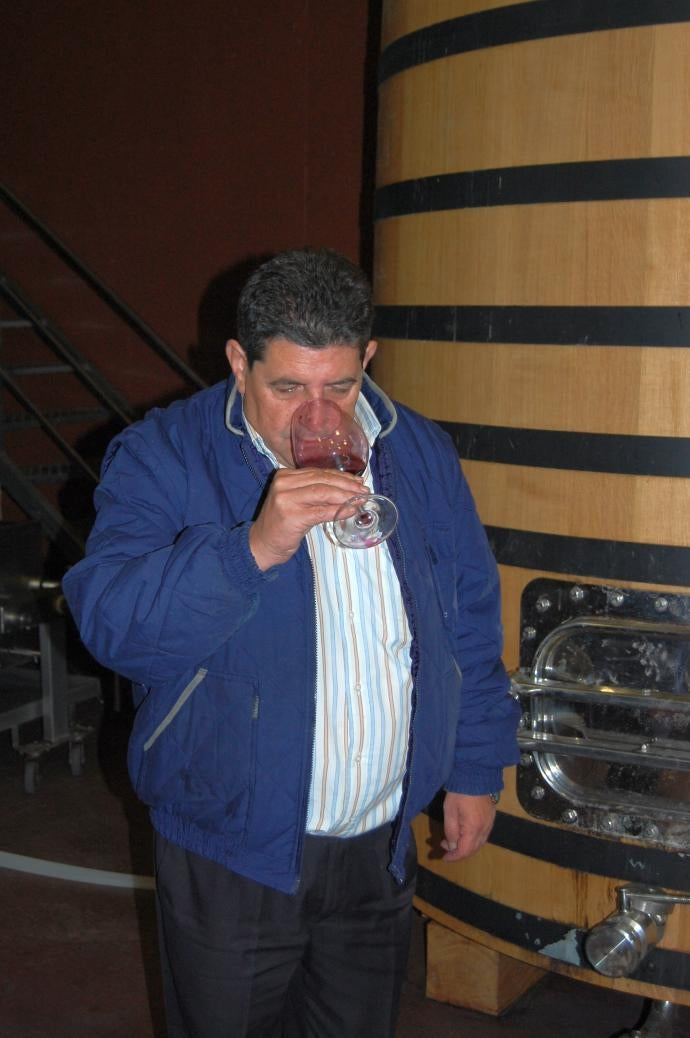Man tasting red wine in front of an oak barrel