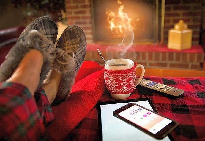 Man's feet in warm slippers next to hot drink, mobile phone and television remote control in front of an open fire
