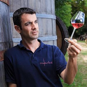 Man looking at glass of rose wine held in his hand