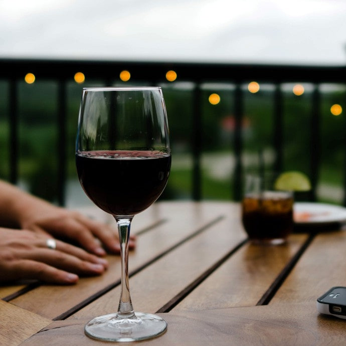 Outdoor table with glass of red wine