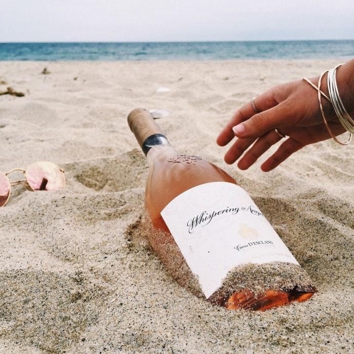 Bottle of Whispering Angel rosé wine in the sand on a beach