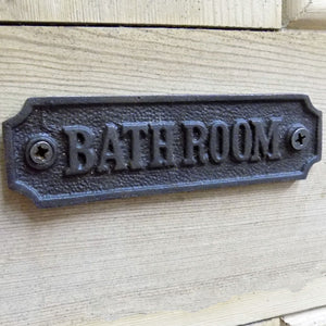Traditional cast metal bathroom door sign