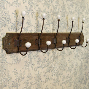 Long row five wall mounted coat hooks on wooden plinth.