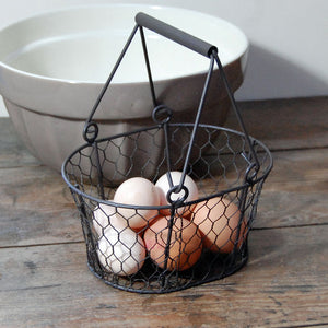 Small traditional vintage style dark brown metal wire egg basket.