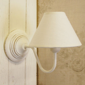 Simple white wooden wall light with cotton coolie lightshade.