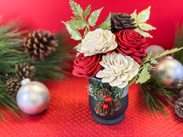 traditional christmas sola flower arrangement in green votive with pinecones
