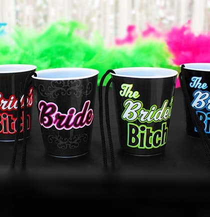 "These plastic shot glasses are a fun party favor for a Bachelorette Party and help identify the bride. The set includes one ""Bride"" and 5 ""Bride's Bitch"" shot glass necklaces."