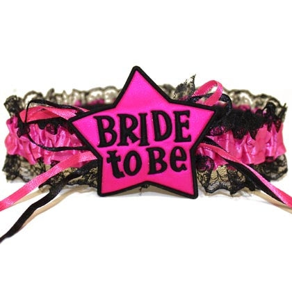 "Let everyone know the Bride is the star of the show on her last night out with this hot pink and black garter! Made of stretch lace and satin, this garter has real lace trim and says ""Bride to be""!"