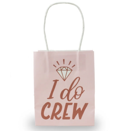 "A pink bag with white handles that say I Do Crew in metallic rose gold.  This 4.5"" mini gift bag is perfect to hand out with goodies or favors."